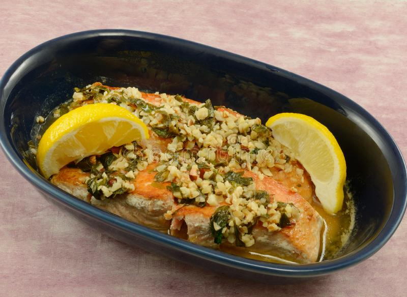 Salmon fish fillets with nuts and lemon. Dinner dish for two of salmon fish fillets with nuts and lemon in blue baking dish royalty free stock photo
