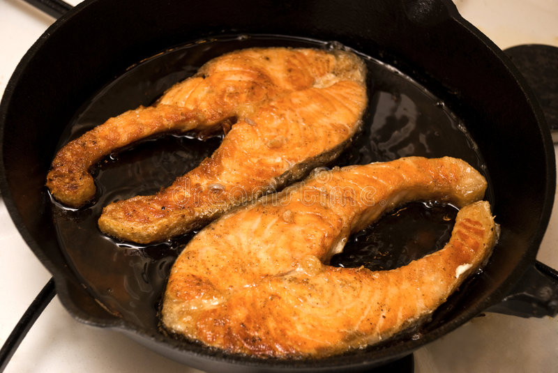 Salmon on a frying pan royalty free stock image
