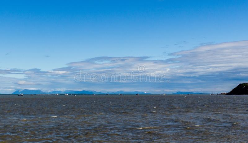 Salmon gillnet fleet and tenders anchored in Bristol Bay off Clarks Point on a windy day. Partly cloudy with bright blue sky royalty free stock photography