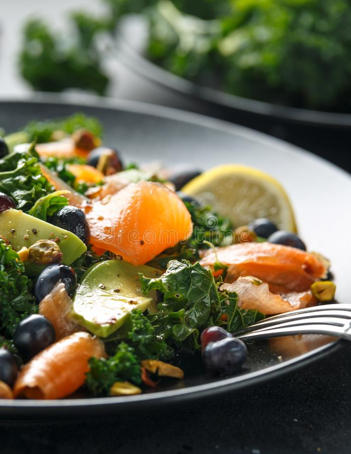 Salmon Kale super food Salad with avocado, pistachio nuts and blueberries on black plate.  royalty free stock photos
