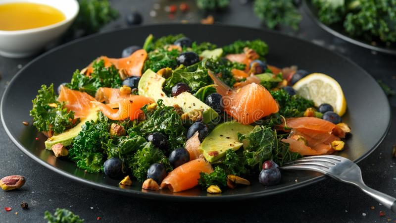 Salmon Kale super food Salad with avocado, pistachio nuts and blueberries on black plate.  royalty free stock photo