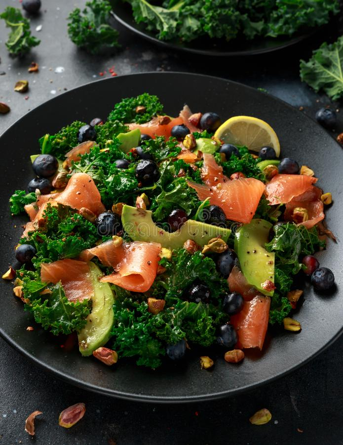 Salmon Kale super food Salad with avocado, pistachio nuts and blueberries on black plate.  stock photography