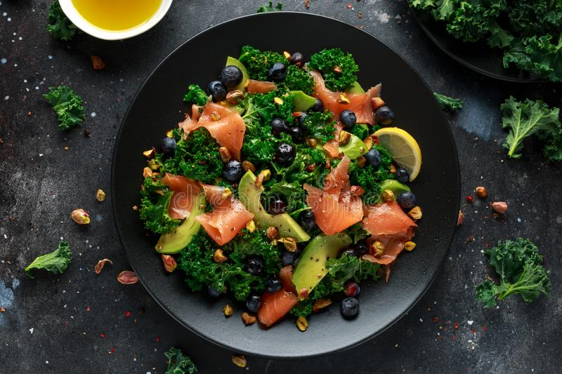 Salmon Kale super food Salad with avocado, pistachio nuts and blueberries on black plate.  stock photo