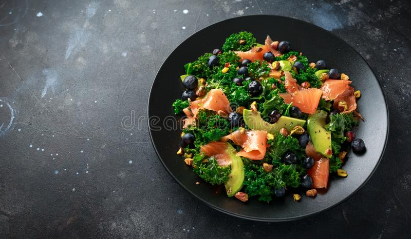 Salmon Kale super food Salad with avocado, pistachio nuts and blueberries on black plate.  stock photos