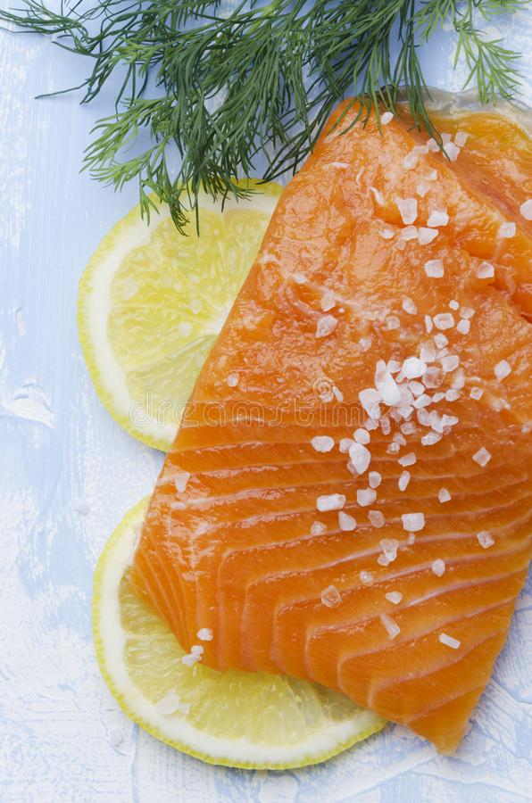 Salmon with lemon,seasalt and dill on bright blue background.Fresh composition of food royalty free stock images