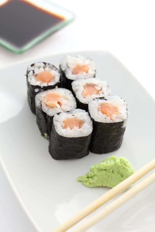Salmon Maki-Sushi mit Essstäbchen und Sojasoße stockfotos
