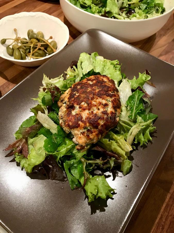 Salmon Meatballs Served caseiro com alcaparras e salada na placa imagem de stock
