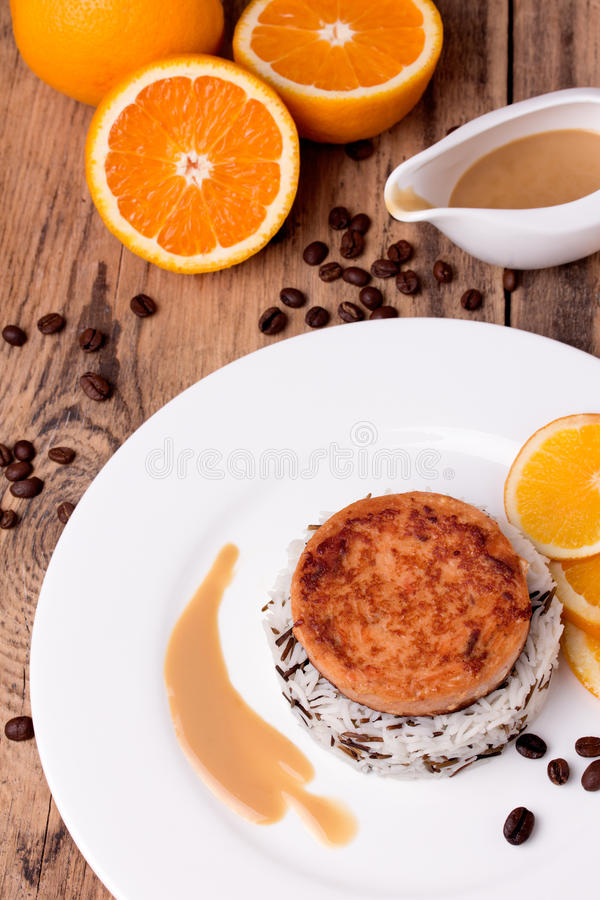 Salmon medallion with mixed cooked rice on white plate stock image
