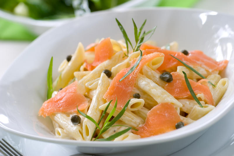 Salmon Pasta. Closeup of plate of Smoked Salmon Penne (tube-shaped pasta) with cappers, tarragon and cheese creamy sauce. Caesar salad and glass of white wine royalty free stock photography