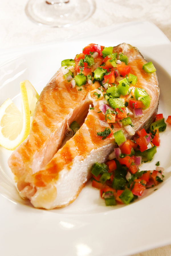 Salmon with pepper salsa. Grilled salmon with pepper salsa on a white plate stock photo