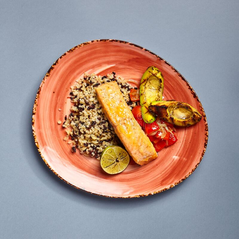 Salmon piece with rice and lime side view stock photo