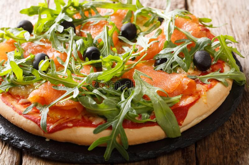 Salmon pizza with fresh arugula, black olives and cheese closeup. horizontal. Salmon pizza with fresh arugula, black olives and cheese closeup on the table royalty free stock photography