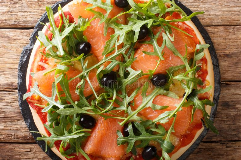 Salmon pizza with fresh arugula, black olives and cheese closeup. Horizontal top view. Salmon pizza with fresh arugula, black olives and cheese closeup on the royalty free stock photo