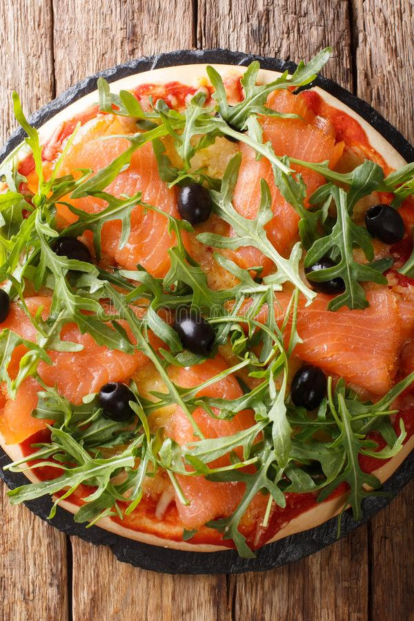 Salmon pizza with fresh arugula, black olives and cheese closeup. Vertical top view. Salmon pizza with fresh arugula, black olives and cheese closeup on the royalty free stock photography