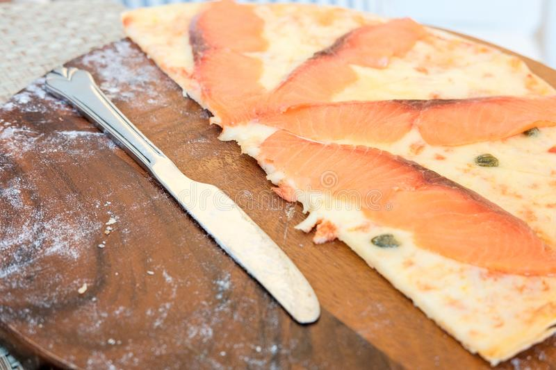 Salmon pizza to eat left. Salmon pizza to eat left on the wood plate and near knife stock photo