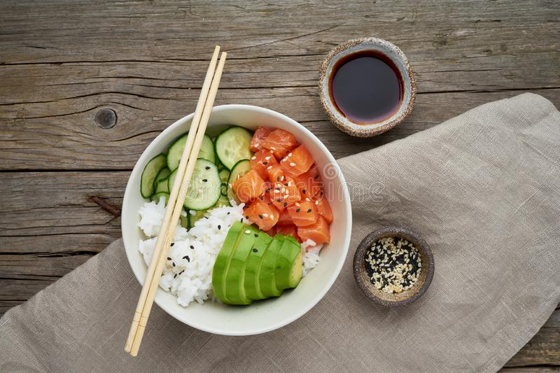 Salmon poke bowl with fresh fish, rice, cucumber, avocado with black and white sesame. Old wooden table. Food concept royalty free stock photos
