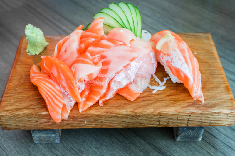 Salmon raw sashimi on wooden table Japanese traditional dish. Closed up royalty free stock photo