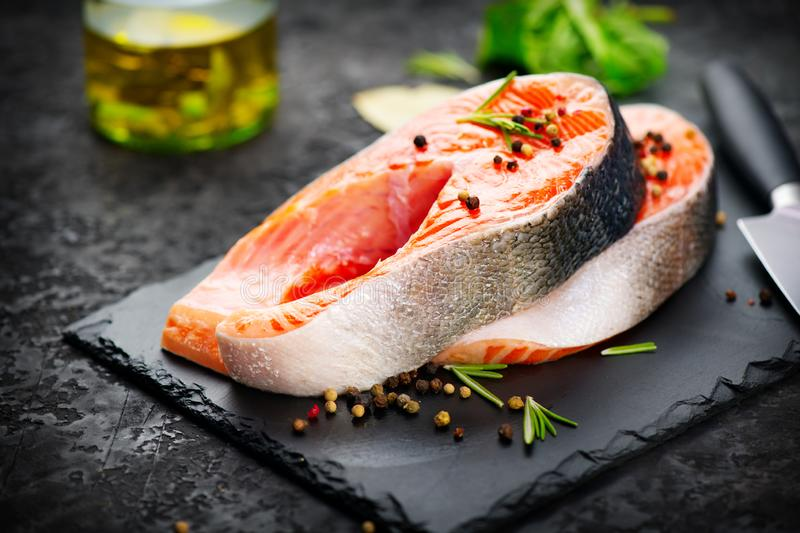 Salmon. Raw trout fish steak with herbs and lemon on black slate background. Cooking, seafood stock images