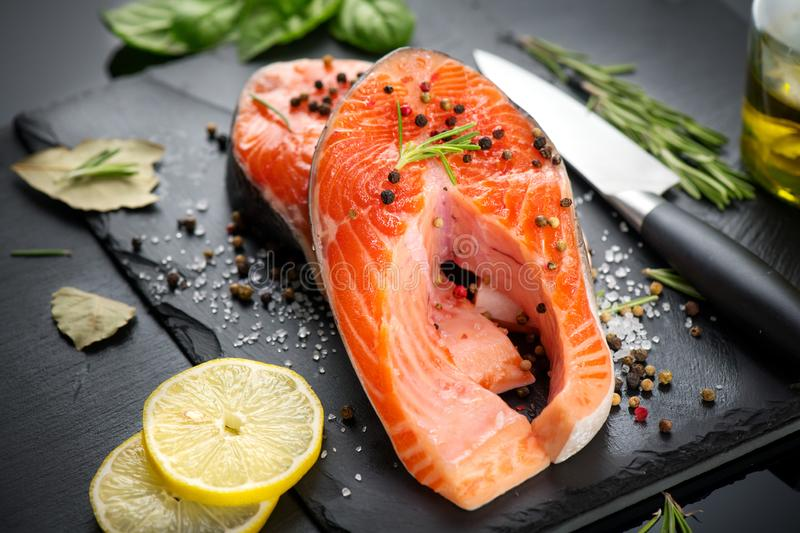 Salmon. Raw trout fish steak with herbs and lemon on black slate background. Cooking, seafood. Healthy eating stock image