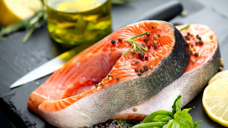 Salmon. Raw trout fish steak with herbs and lemon on black slate background. Cooking stock photos