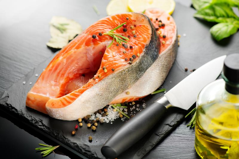 Salmon. Raw Trout Red Fish Steak served with Herbs and Lemon and olive oil on slate. Cooking Salmon, sea food. Healthy eating. Concept stock photos