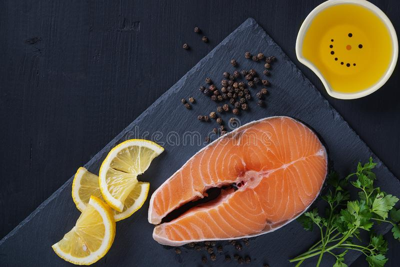 Salmon. Raw Trout Red Fish Steak served with Herbs and Lemon and olive oil on slate. Cooking Salmon, sea food. Healthy eating royalty free stock photo