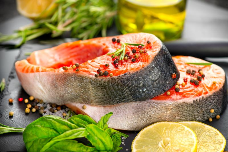Salmon. Raw Trout Red Fish Steak served with Herbs and Lemon and olive oil on slate. Cooking Salmon, sea food. Healthy eating. Concept royalty free stock photos