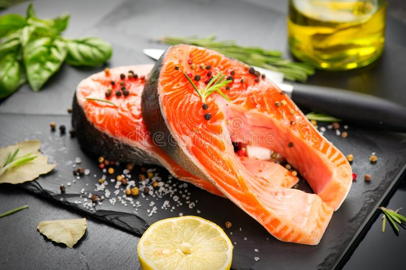 Salmon. Raw Trout Red Fish Steak served with Herbs and Lemon and olive oil on slate. Cooking Salmon, sea food. Healthy eating. Concept royalty free stock image