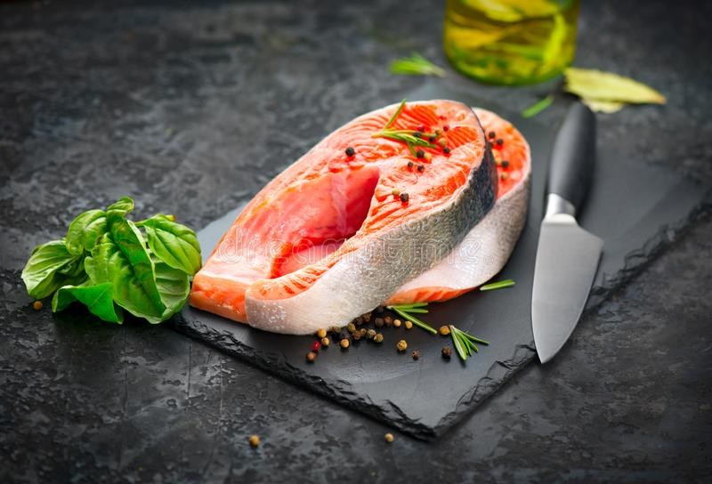 Salmon. Raw Trout Red Fish Steak served with Herbs, Lemon and olive oil on slate. Cooking Salmon, sea food. Healthy eating. Concept, Mediterranean cuisine stock photo