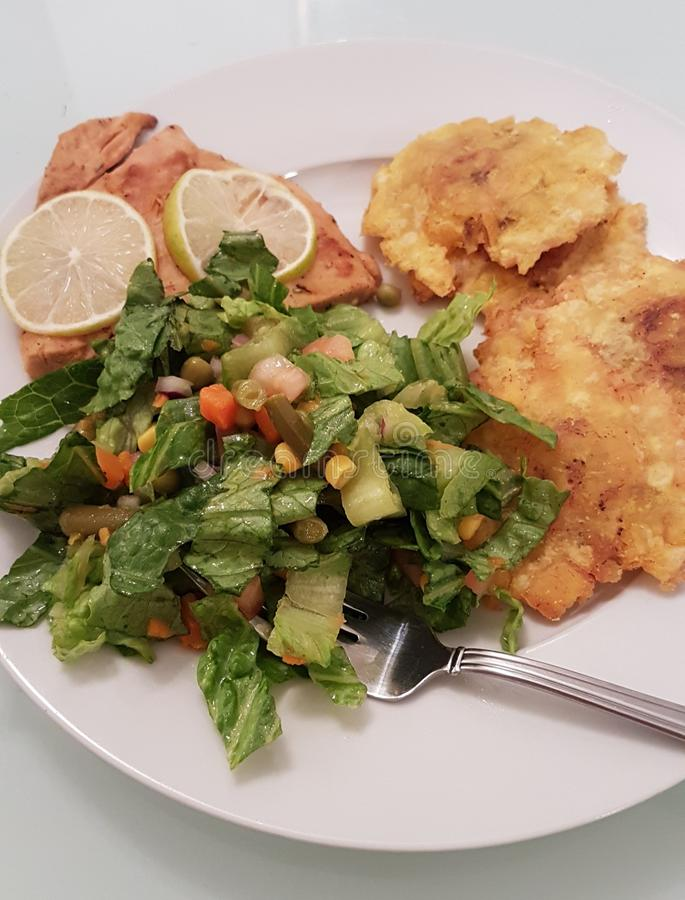 Salmon, salad and fried plantain. royalty free stock photography
