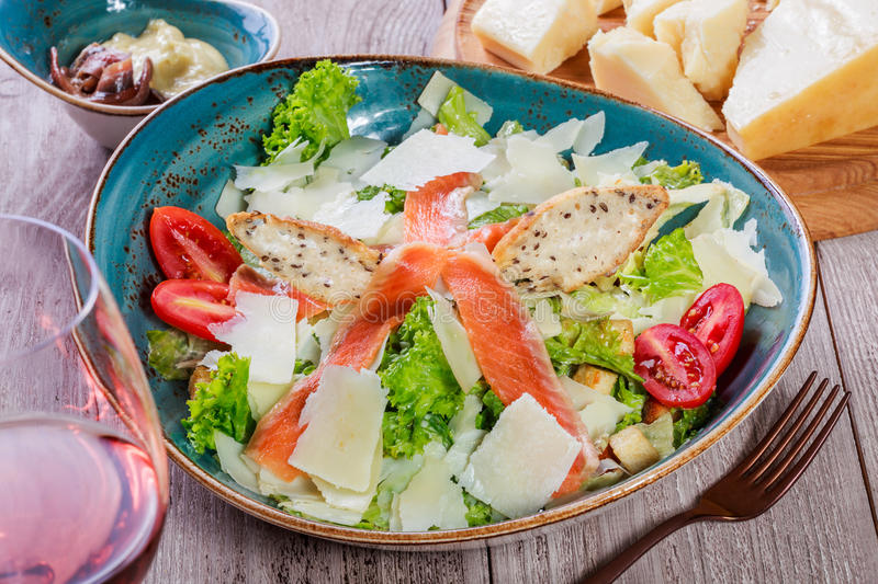 Salmon salad with tuna sauce, parmesan cheese, croutons, tomatoes, mixed greens on wooden background. Mediterranean food stock images