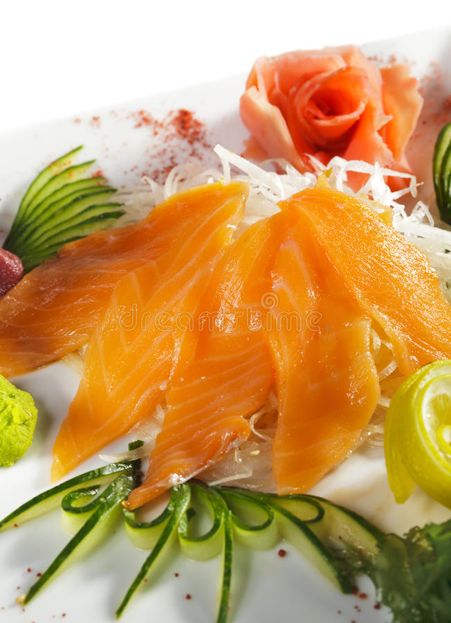 Salmon Sashimi. Sliced Raw Salmon on Daikon (White Radish) with Seaweed and Cucumber stock photos