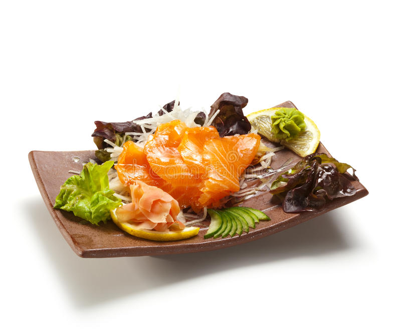 Salmon Sashimi. Sake (fresh raw salmon) on Daikon (White Radish). Garnished with Ginger, Wasabi, Seaweed, Cucumber, Salad Leaf and Lemon stock image