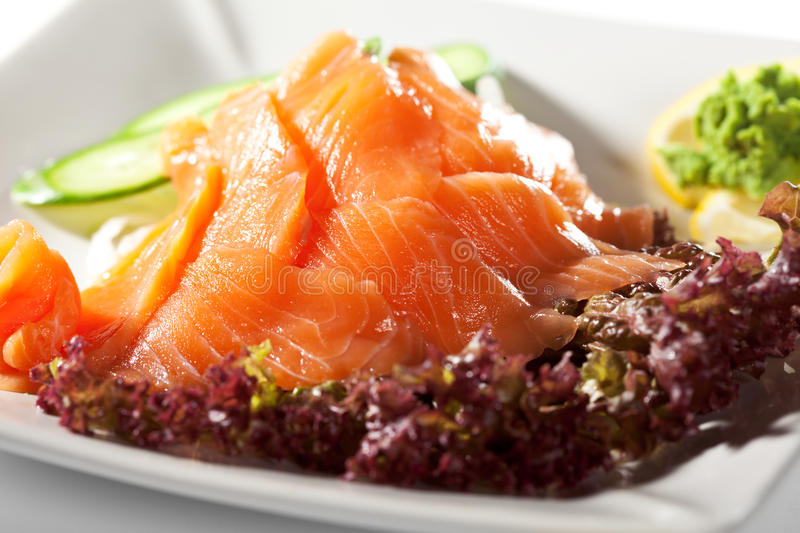 Salmon Sashimi. Sliced Raw Salmon on Daikon (White Radish) with Seaweed and Cucumber royalty free stock image