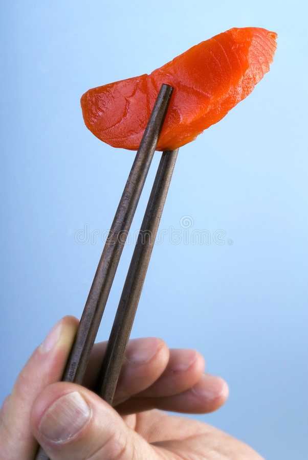 Salmon Sashimi. This image shows a piece of salmon sashimi being held by chopsticks royalty free stock image