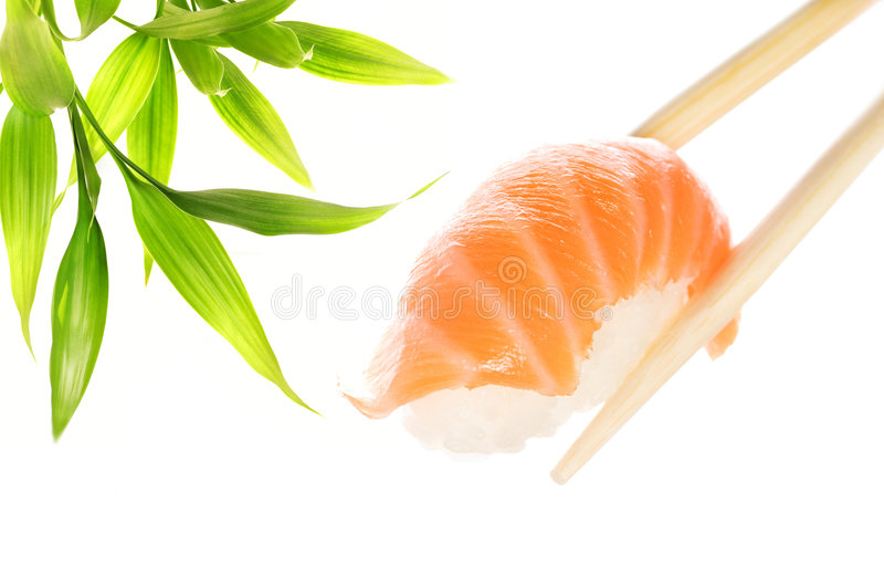 Salmon sashimi. Wooden chopsticks holding salmon sashimi royalty free stock images