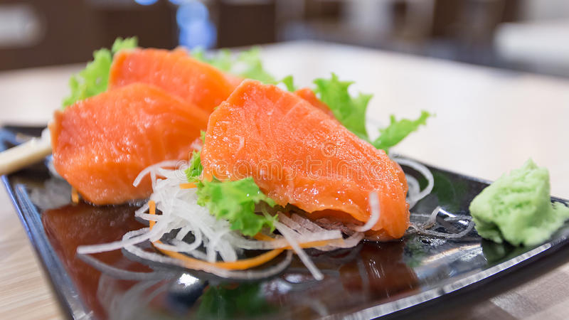 Salmon sashimi on a dish with vegetables. Select focus royalty free stock image