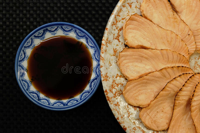 Salmon sashimi grill flower shape on circle plate on right black background royalty free stock images
