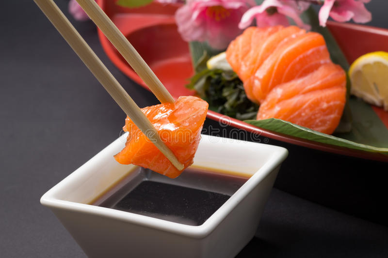 Salmon sashimi. Isloated on white background and on plate with chopsticks royalty free stock image