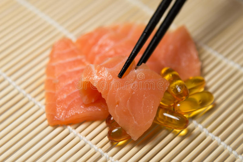 Salmon Sashimi mixed with Fish oil capsules with chopstick grab royalty free stock photos
