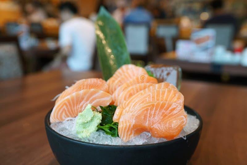 Salmon sashimi - Salmón fresco crudo cortado en rodajas servido en plato negro con wasabi y rábano triturado, mano sosteniendo pa foto de archivo