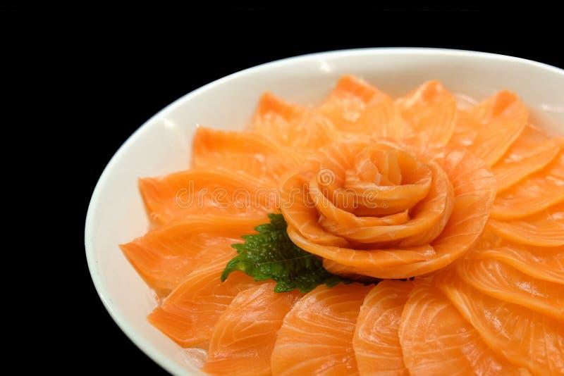 Salmon sashimi serve on flower shape on ice white bowl boat on black isolated background royalty free stock images