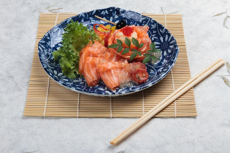 Salmon sashimi served with lime sauce, potato salad and ikura served in panted ink plate with chopstick on makisu Meal mat stock images