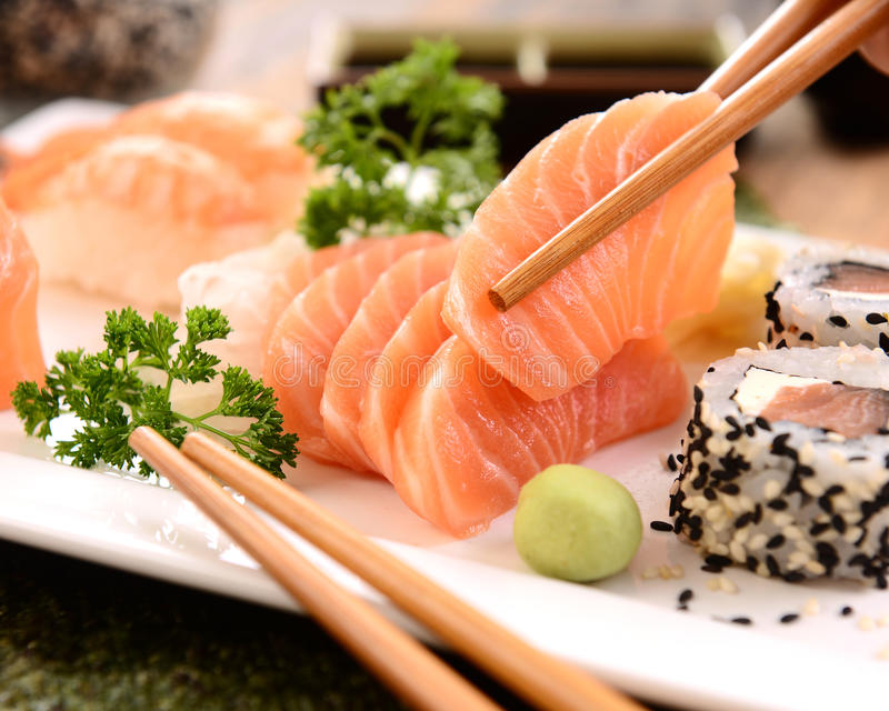 Salmon sashimi. A tasty slice of salmon sashimi on chopsticks stock image