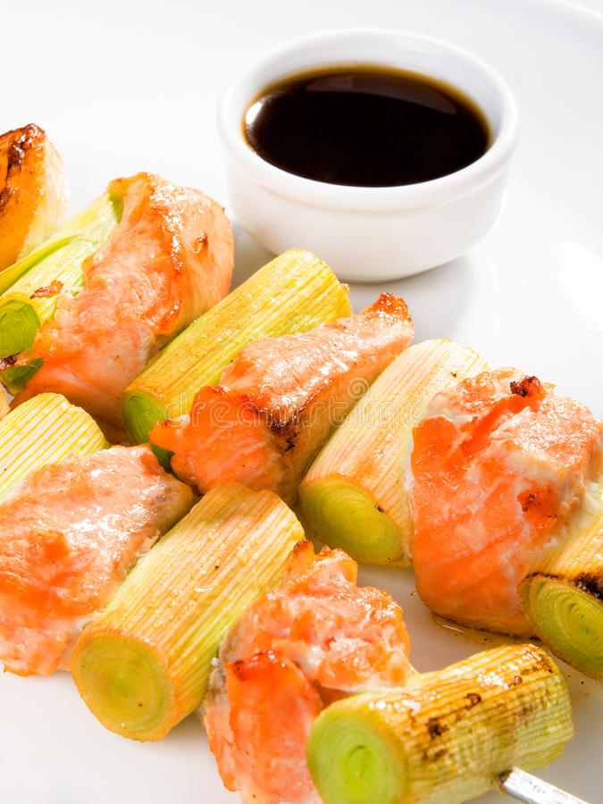 Salmon skewers with leek. Isolated on white background stock photo