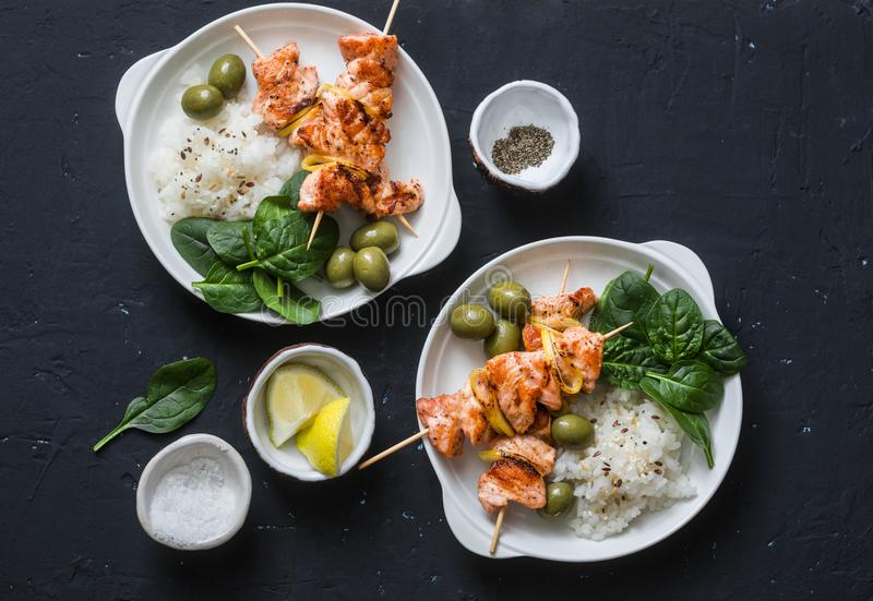 Salmon skewers, olives, spinach, rice - healthy lunch table. Grilled salmon fish skewer and side dish on a dark background. Top view stock images