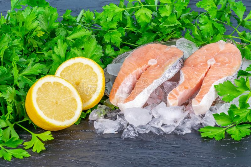 Salmon with slices of lemon and parsley on the dark table. royalty free stock photo