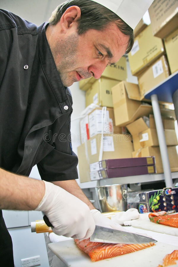 A salmon slicing. A professional chef in black uniform and a white chef's hat is working on a restaurant kitchen. He is carefully slicing red salmon for stock photos