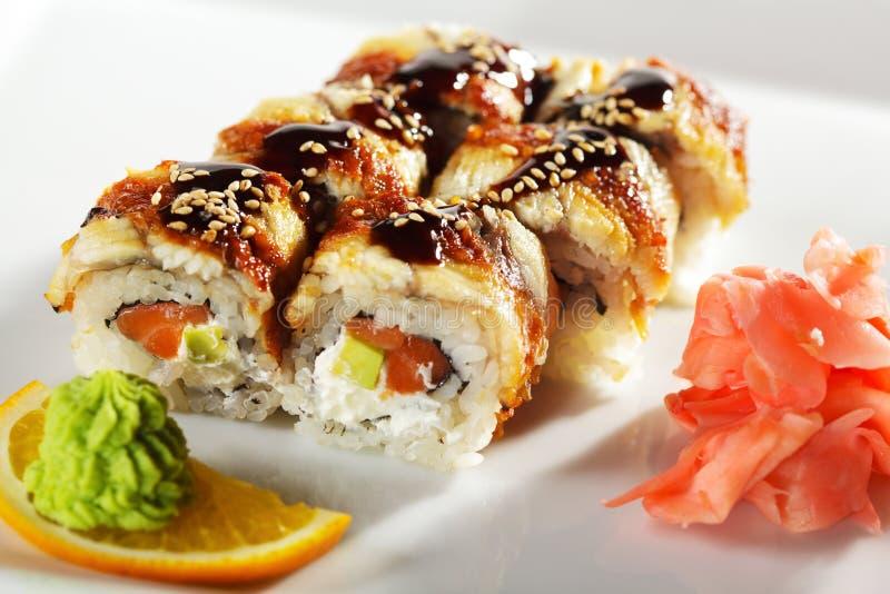 Salmon and Smoked Eel Maki Sushi. Roll made of Fresh Raw Salmon, Smoked Eel, Cream Cheese and Avocado inside. Unagi (Eel) outside stock photography
