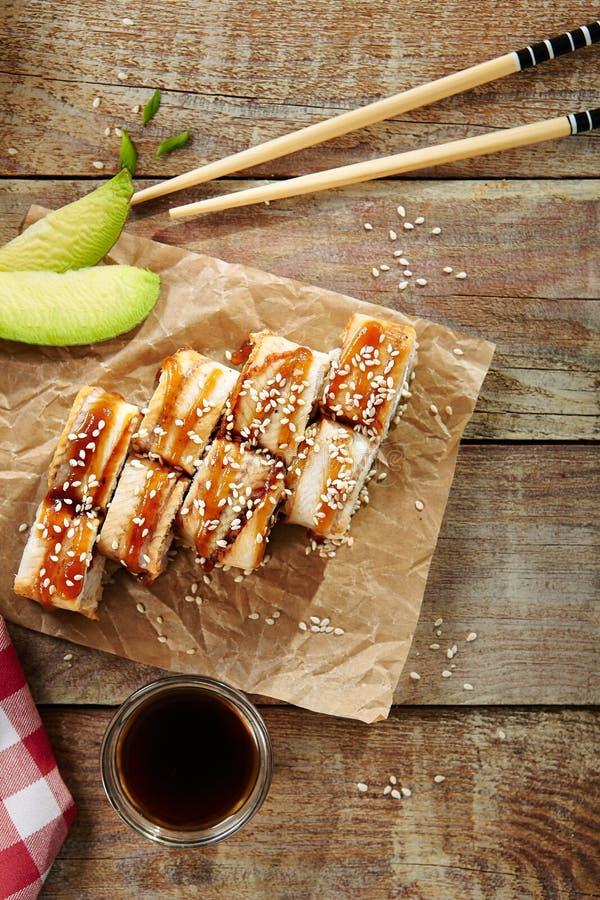 Salmon and Smoked Eel Sushi Roll. With Pickled Daikon, Sauce, Sesame Close Up. Macro Photo of Nori Maki, Norimaki or Futomaki with Unagi and Raw Fish, Seaweed royalty free stock image
